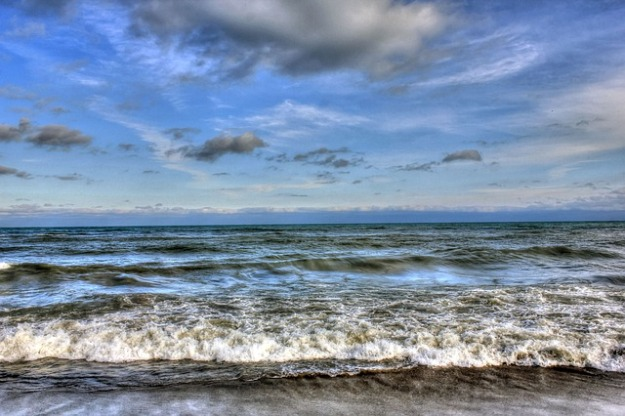 rolling waves of lake michigan hit shore. Dark clouds mingle with light ones in a blue sky. A bank of clouds in the far distance on the horizon